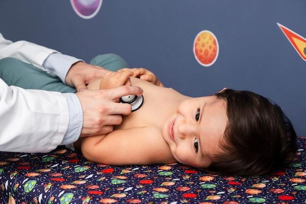 De baby die van de close-up met stethoscoop wordt onderzocht Gratis Foto