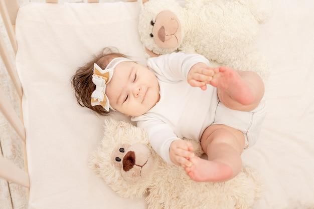 De baby is zes maanden oud in een wieg in een wit rompertje met een teddybeer Premium Foto
