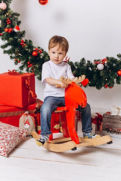 De babyjongen die van de zuigeling thuis in kerstmisavond speelt. vakantie decoraties, oudejaarsavond met kleurrijke lichten zijn op de achtergrond Premium Foto