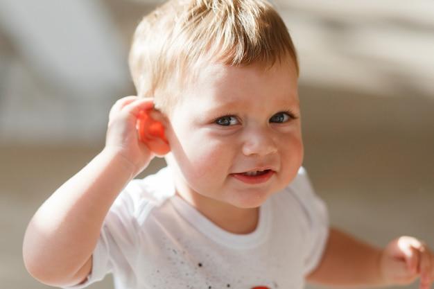 De babyjongen luistert om een hand aan zijn oor te leggen. Gratis Foto