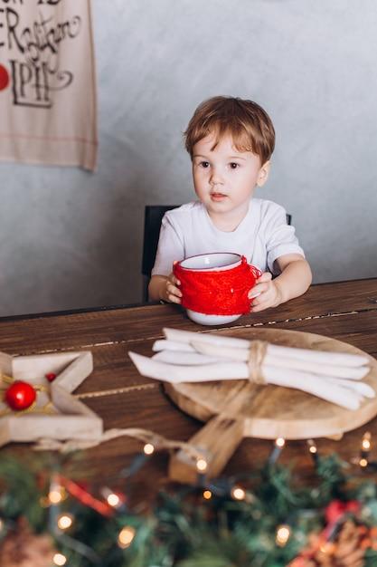 De babyjongen van de zuigeling in gebreide hoed die thuis in kerstmisavond speelt. vakantie decoraties, oudejaarsavond met kleurrijke lichten zijn op de achtergrond Premium Foto