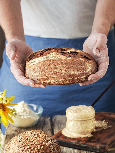 De bakker houdt zelfgemaakt ambachtelijk brood in zijn handen Gratis Foto