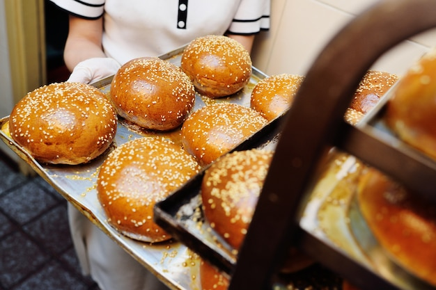 De bakkerijarbeider die van de vrouw een dienblad van verse ronde broodjes voor burgers met sesamzaden dicht tegenhouden Premium Foto