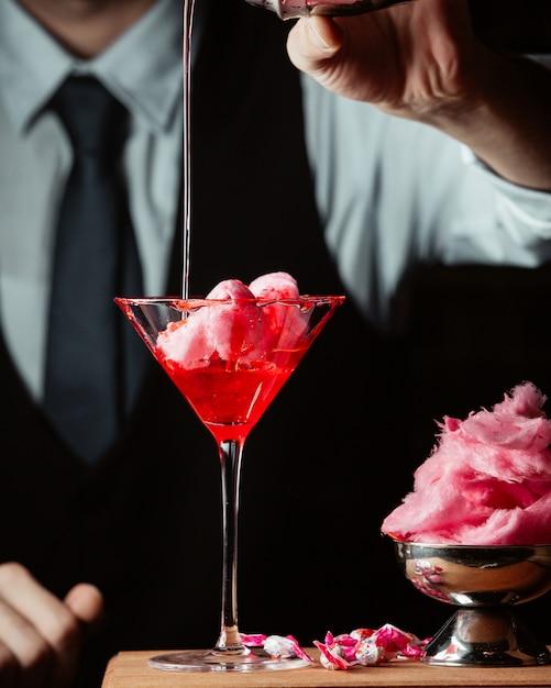 De barman bereidt zoete katoenen cocktail in martini-glas Gratis Foto