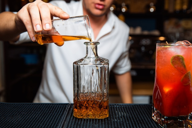 De barman giet whisky in een karaf. Premium Foto