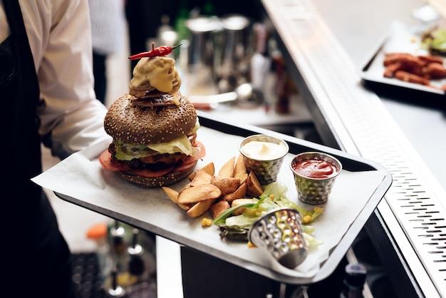 De barman serveert een hamburger voor mensen. Premium Foto