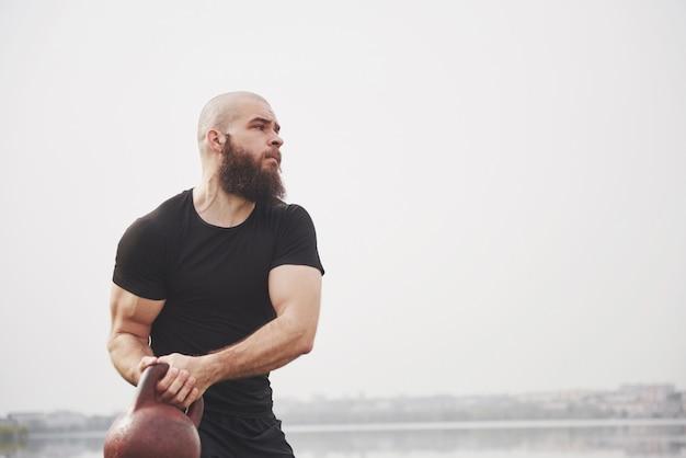 De bebaarde jonge man houdt zich bezig met buitensporten Gratis Foto