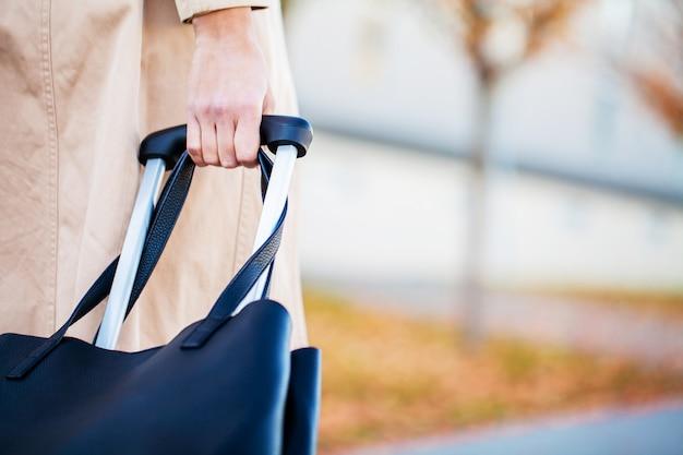 De bebouwde toeristenvrouw van de beeldreiziger kruiste benen in de zomer vrijetijdskleding met koffer op weg in stad openlucht. meisje dat naar het buitenland reist om op weekenduitje te reizen. toerisme reis levensstijl Premium Foto