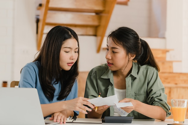 De bedrijfs aziatische lesbische lgbtq vrouwen koppelen thuis rekening Gratis Foto