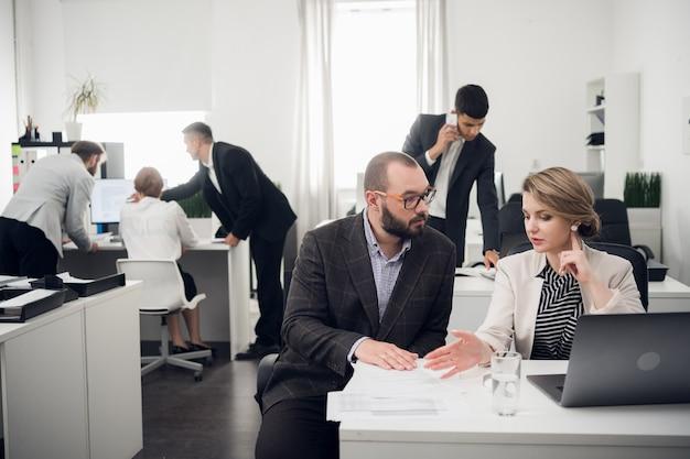 De bedrijfscoach instrueert stagiaires in een ruim kantoor. opleiding van nieuwkomers, stages bij een groot bedrijf Premium Foto