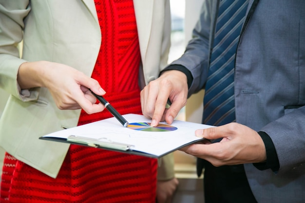 De bedrijfsman en de werkende vrouw spreken over het werk aangaande document bladrapport, bedrijfsconcept. Premium Foto