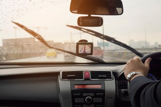 De bedrijfsmens drijft een auto in regenende dag met bewegende wisserbladen Gratis Foto