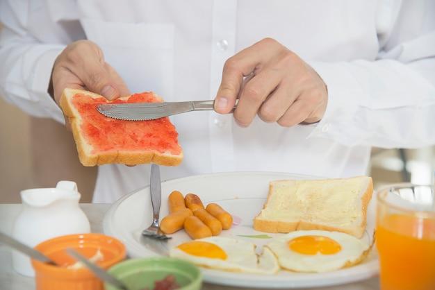 De bedrijfsmens eet het amerikaanse die ontbijt in een hotel wordt geplaatst Gratis Foto