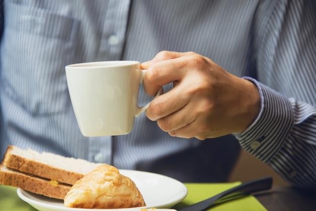 De bedrijfsmens eet het amerikaanse ontbijt dat in een hotel wordt geplaatst Gratis Foto