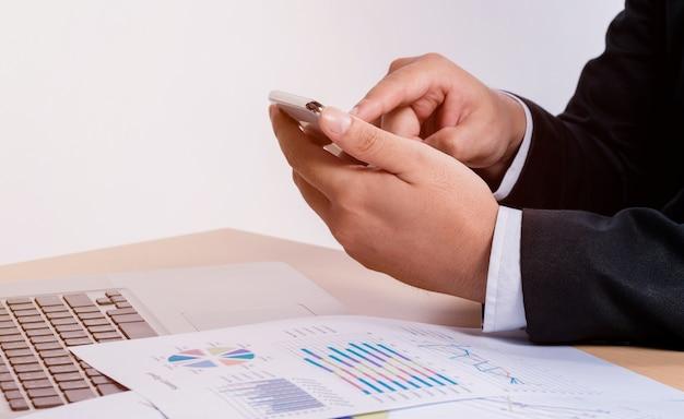 De bedrijfsmens raakt de mobiele telefoon op het team van de vergaderingslijst om op het kantoor te werken Premium Foto