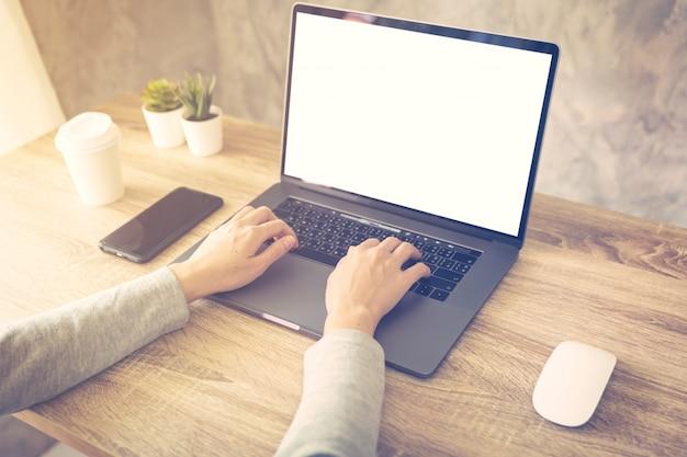 De bedrijfsvrouw die laptop computer met behulp van doet online activiteit op houten lijst thuis kantoor. Premium Foto