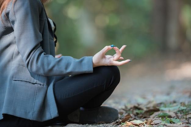 De bedrijfsvrouw die yogameditatie in het natuurreservaat doen, sluit omhoog. Premium Foto