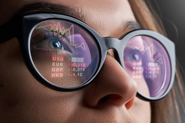 De bedrijfsvrouw met glazen bekijkt beurskoersen en wisselkoersen tijdens de financiële crisis Premium Foto