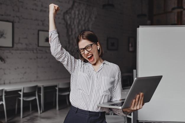 De bedrijfsvrouw met in hand laptop is tevreden met succes. portret van een vrouw in glazen en gestreepte blouse enthousiast schreeuwen en winnende gebaar maken. Gratis Foto