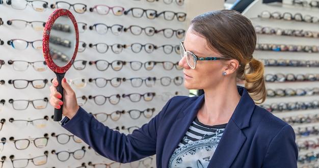 De bedrijfsvrouw probeert glazen voor een spiegel in een optiekopslag Premium Foto