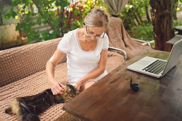 De bejaarde hogere vrouw met huiskat gebruikt draadloze hoofdtelefoons die online met laptop computer werken Premium Foto