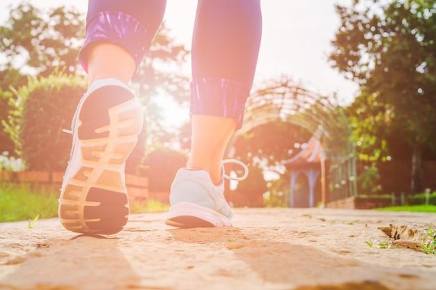 De benen die van de jonge geschiktheidsvrouw in de ochtend bij openlucht openbaar park lopen. Premium Foto