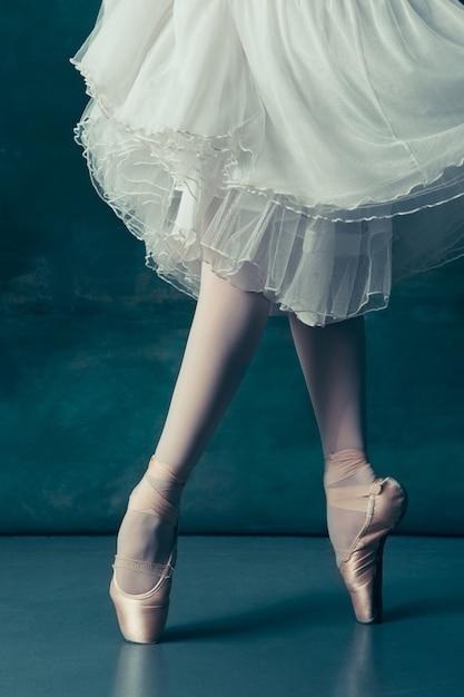 De benen van close-upballerina's in pointes op de grijze houten vloer Gratis Foto