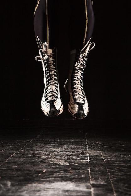 De benen van de gespierde man met springtouw kickboksen training op zwart Gratis Foto