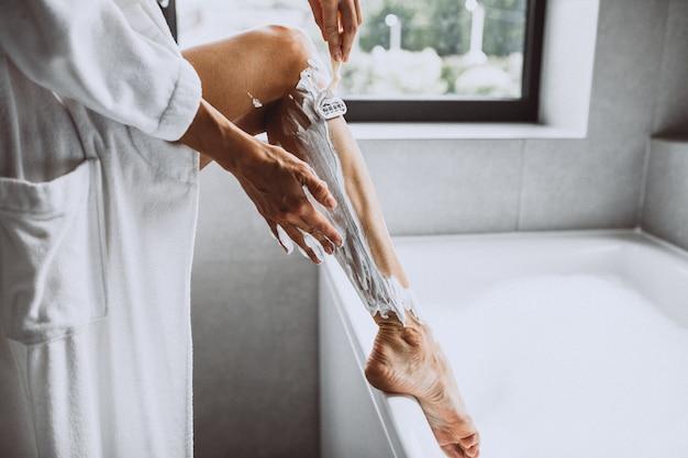 De benen van de vrouwenwas thuis in badkamers Gratis Foto