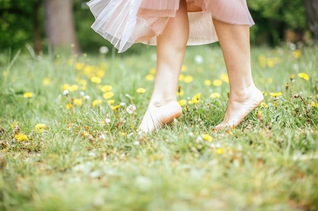 De benen van jonge blootvoetse vrouwen die roze kleding dragen die zich op één been op groen gras met gele bloemen bevinden, sluiten omhoog Premium Foto