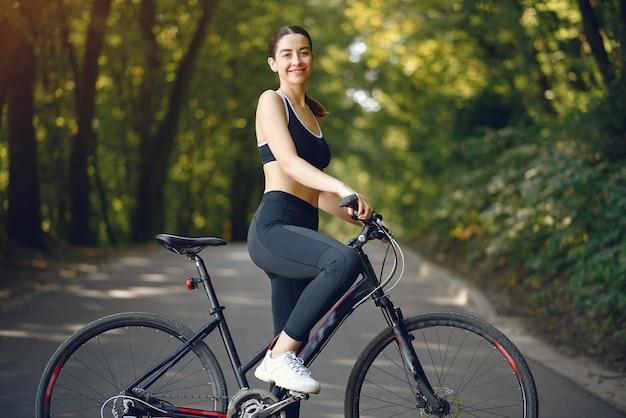De berijdende fietsen van de sportenvrouw in de zomerbos Gratis Foto