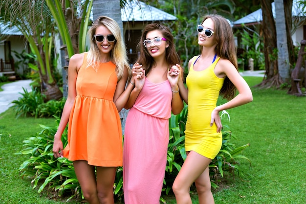De beste vrienden van sexy meiden die plezier hebben op vakantie in een exotisch warm tropisch land, heldere hipster levendige strandjurken dragen, gelukkige emoties, glimlachen en lachen, tuinfeest, ontspannen, dansen, vreugde. Gratis Foto