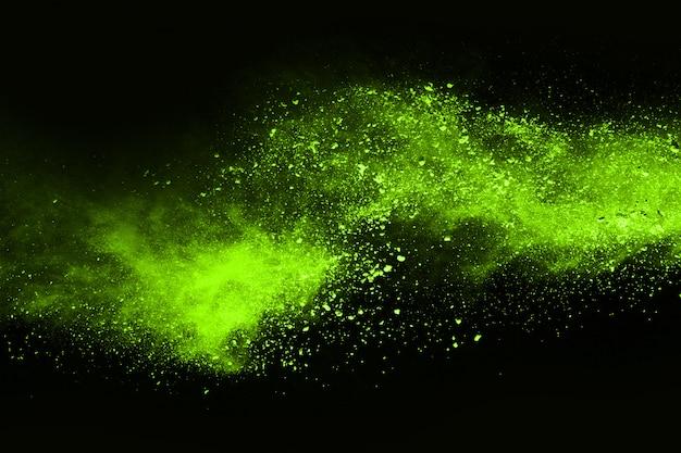 De beweging van abstracte stofexplosie bevroren groen op zwarte achtergrond. Premium Foto