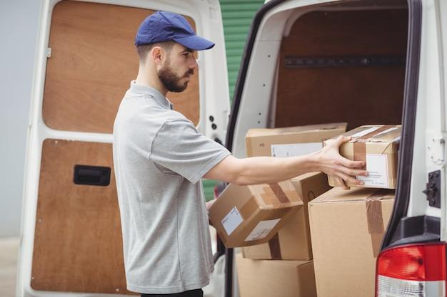De bezorger die van de levering pakketten houdt om zijn bestelwagen te laden Premium Foto
