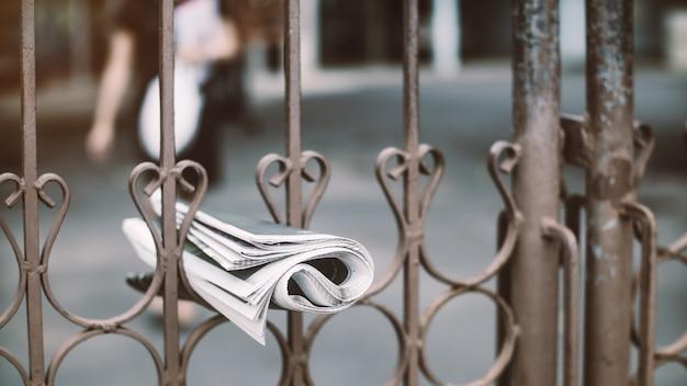 De bezorging van een krant hangt aan het hek en de vrouw loopt om het te houden. Premium Foto