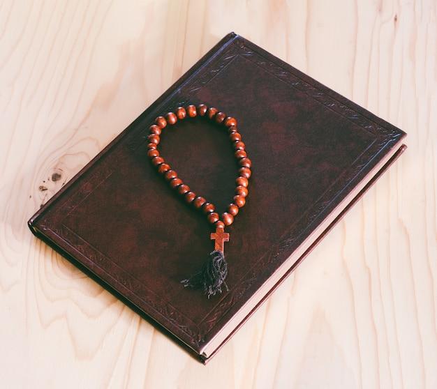 De bijbel en houten rozenkrans op de tafel, bovenaanzicht close-up Premium Foto