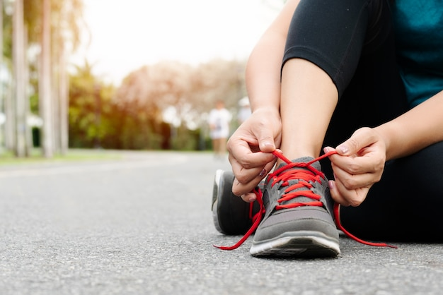 De bindende schoenveter van de sportvrouw alvorens te lopen Premium Foto
