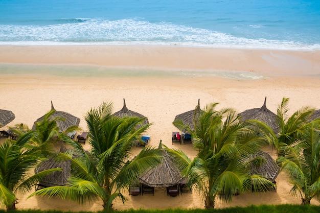 De bladeren van bruine rieten parasols op het strand Premium Foto