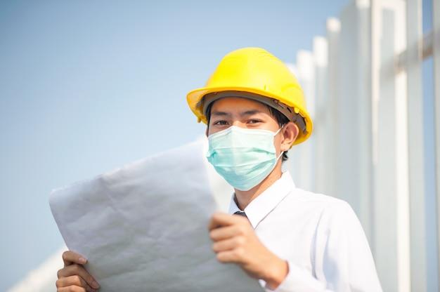 De blauwdruk van de ingenieursholding draagt het medische werk van het gezichtsmasker bij bouwwerf Premium Foto