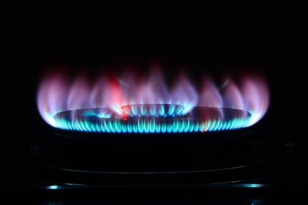 De blauwe vlam van een fornuisbrander in het donker Premium Foto