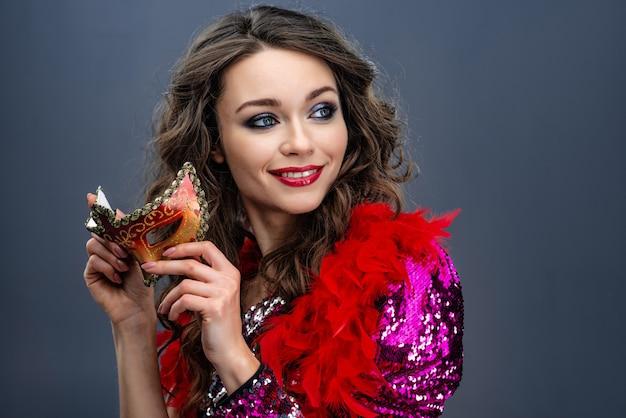 De blijde vrouw houdt een carnavalsmasker in een schitterende jurk en een boa om haar nek Premium Foto