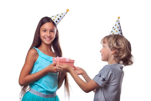 De blonde jongen in feestelijke document hoed geeft heden in giftvakje aan gelukkig meisje op haar verjaardagspartij Premium Foto