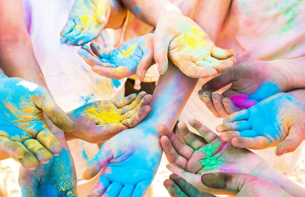 De bos van kleurrijke handen van vrienden groepeert zich het hebben van pret bij strandpartij op de zomervakantie van het holikleurfestival Premium Foto