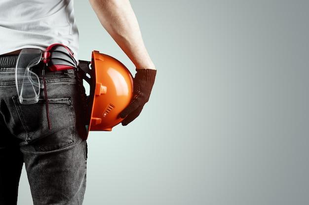De bouwer, de architect houdt in zijn hand een bouwhelm Premium Foto
