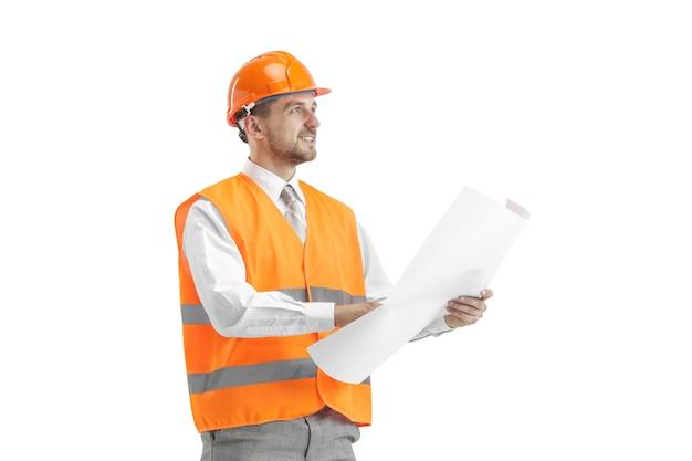 De bouwer in een bouwvest en een oranje helm die zich op witte muur bevindt. veiligheidsspecialist, ingenieur, industrie, architectuur, manager, beroep, zakenman, baanconcept Gratis Foto