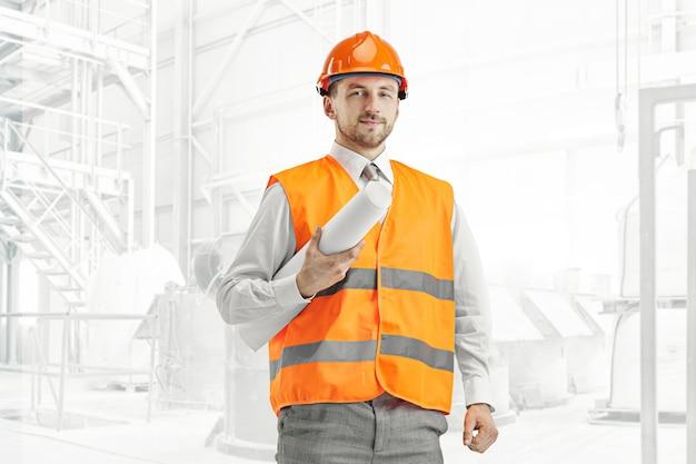 De bouwer in een bouwvest en een oranje helm status. veiligheidsspecialist, ingenieur, industrie, architectuur, manager, beroep, zakenman, baanconcept Gratis Foto