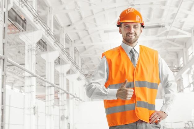 De bouwer in oranje helm tegen industrieel Gratis Foto