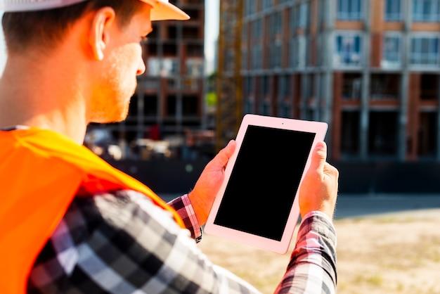 De bouwingenieur die van de close-up zijaanzicht tablet gebruiken Gratis Foto