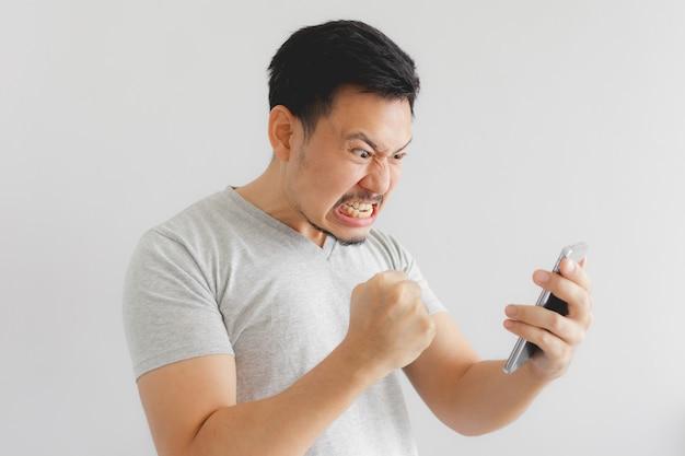De boze mens in grijze t-shirt wordt gek op smartphone. Premium Foto