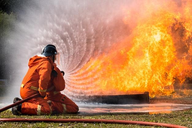 De brandbestrijder bespat water om hydrant af te vuren Premium Foto
